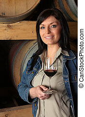 Brunette stood buy wine barrels