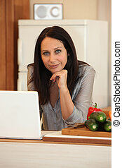 Brunette stood in the kitchen with computer