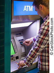 Brunette student withdrawing cash