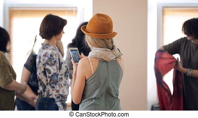 Brunette stylist explains to women how to tie warm red scarf in room.