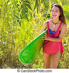 Brunette surfer girl walking in the jungle with surfboard