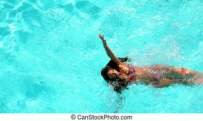 Brunette swimming across the pool on sunny day in slow...
