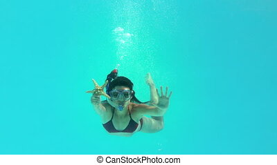 Brunette swimming underwater
