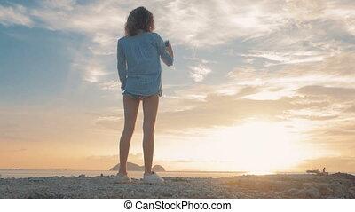 Brunette taking a photo of the sunset, steadicam shot