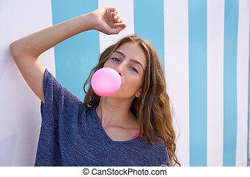 Brunette teen girl bubble gum in blue stripes wall -...