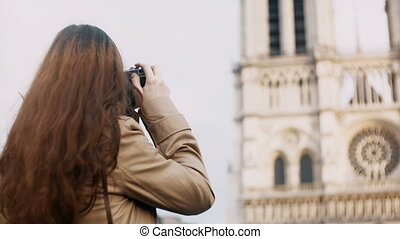 Brunette teenager taking photo of Notre Dame on retro film...