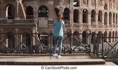 Brunette tourist woman stands back to camera in Rome, Italy taking photos of the Colosseum with smartphone. Slow motion.