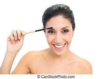 Brunette using an eyebrow brush and smiling