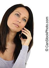 Brunette using her mobile telephone