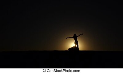 Brunette veil in her hands dancing belly dance on the beach. Silhouette. Slow motion
