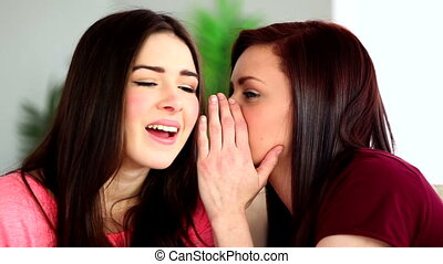 Brunette whispering secret to her shocked friend on the...