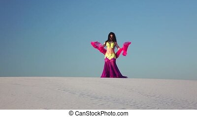 Brunette with a veil in her hands dances a belly dance in the desert. Slow motion