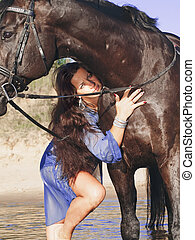 brunette with black horse in water