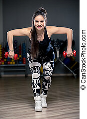 brunette with dumbbells during training portrait in gym