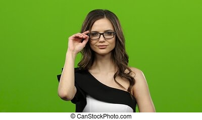 Brunette with glasses starts flirting, she smiles sweetly. Green screen