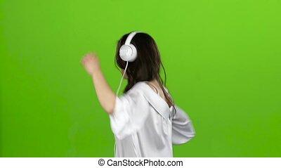 Brunette with headphones in her ears is having fun. Green screen. Slow motion