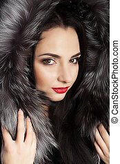 Brunette with long beautiful hair, dressed in a coat. Cool young girl. Professional makeup. Winter theme. Red lips.