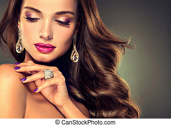 Brunette with long curled hair. Luxury fashion style, nails manicure, cosmetics, make-up.