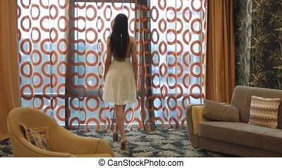 Brunette with long hair in a white dress and heels goes to the panoramic window and opens the curtains