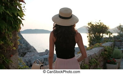 Brunette with luxurious curls and hat stand with back and...
