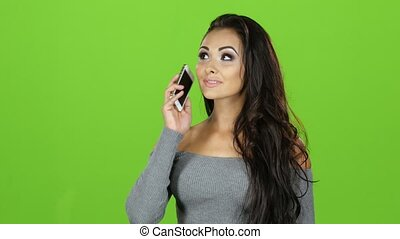 Brunette with smile talking on mobile phone, green screen background