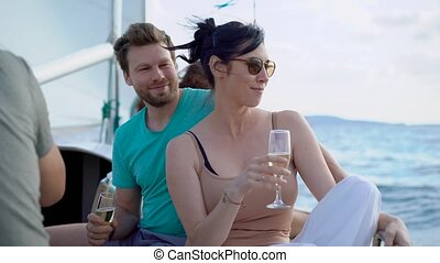 brunette woman and brown-haired man sitting on a board of yacht and drinking champagne in the summer day