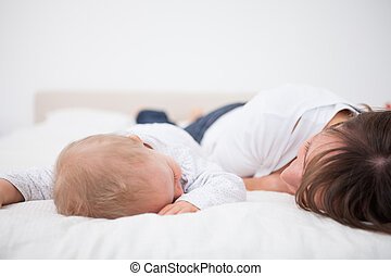 Brunette woman and her baby lying together