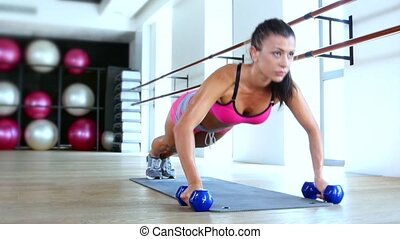 Brunette woman at gym push up push-up workout exercise with dumbbells