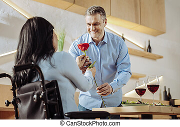 Brunette woman being presented with a flower