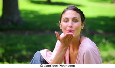 Brunette woman blowing a kiss