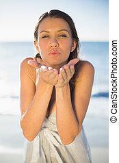 Brunette woman blowing an air kiss