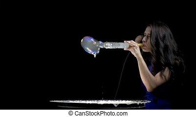 Brunette woman blowing smoky soap bubbles