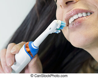 brunette woman brushing teeth