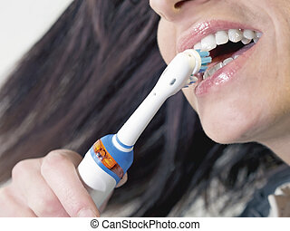 brunette woman brushing teeth with electric toothbrush -...
