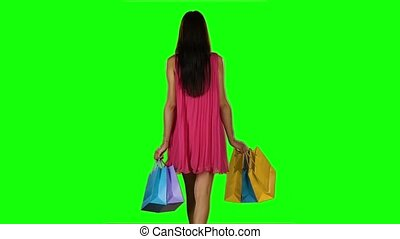 Brunette woman buying clothes. Shopping bags. Green screen. Slow motion