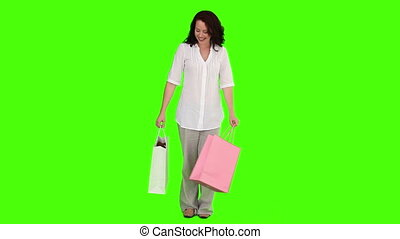 Brunette woman buying clothes against a green screen