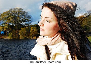 Brunette woman by a lake, autumn/winter scene