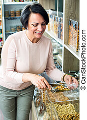 Brunette woman choosing nuts