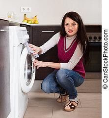 brunette woman cleaning washing machine
