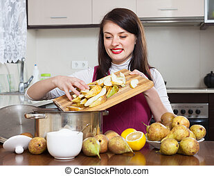 Brunette woman cooking pear jam in the kitchen