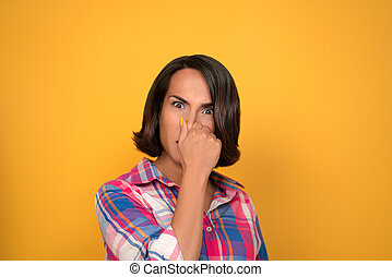 Brunette woman covers her nose with her hand. The unpleasant smell of the concept. Shooting in the studio on a yellow background. High quality photo
