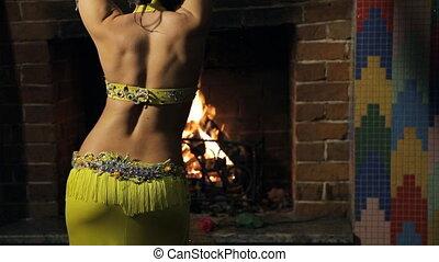 brunette woman dances belly dance indoor. View from back.