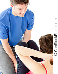 Brunette woman doing sit-ups assited by her personal trainer
