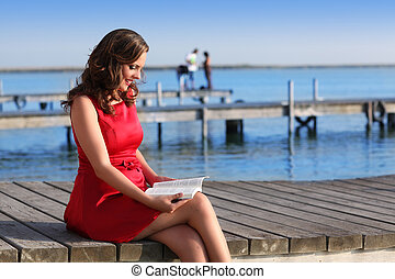 Brunette woman dress in red reading a book
