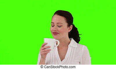 Brunette woman drinking a cup of tea against a green screen