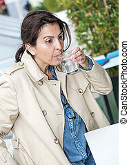 Brunette woman drinking a glass of water