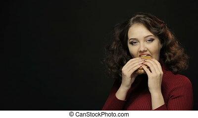 Brunette woman eating burger, closeup shooting