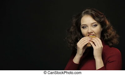 Brunette woman eating burger, closeup shooting