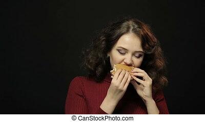 Brunette woman eating hamburger, closeup shooting