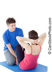 Brunette woman exercising assisted by a personal coach